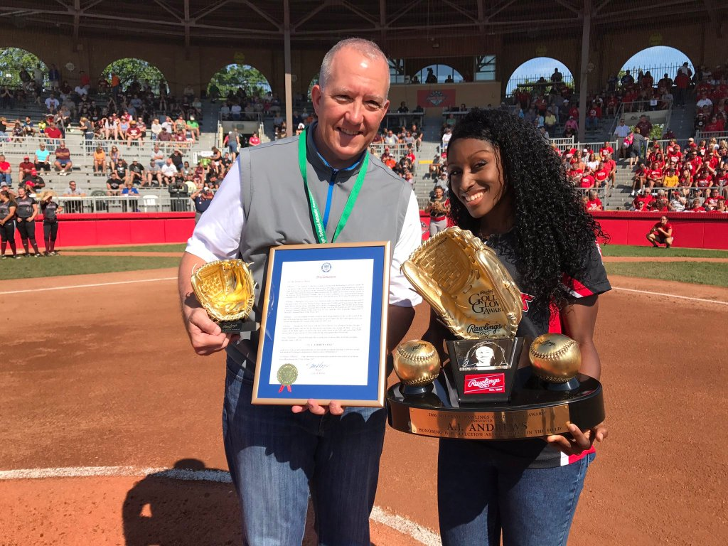 AJ Andrews, holding the Rawling's Golden Glove Award and standing with Akron Mayor Dan Horrigan