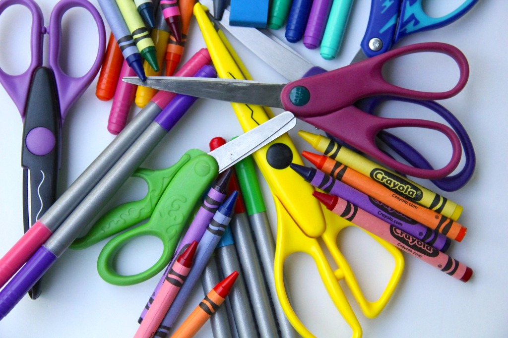 crayons, scissors and markers scattered on a white table
